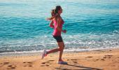 Mujer corriendo por la orilla del mar