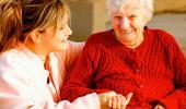 Una anciana dependiente sonríe junto a su cuidadora