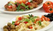 Platos con espagueti con verduras y aceitunas y pollo