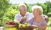 Una pareja mayor disponiéndose a comer fruta al aire libre