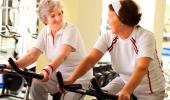Dos mujeres mayores realizan ejercicio en bicicleta estática