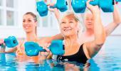 Personas mayores realizan ejercicio en el agua con una monitora