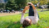 Mujer consulta su smartphone tumbada en el césped en un parque
