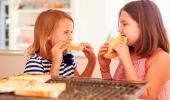 Dos niñas comen pan tostado
