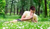 Un joven alérgico se suena la nariz en el campo