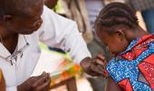 Un sanitario vacuna a una niña contra la fiebre amarilla