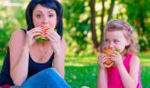 Madre e hija comiendo hamburguesa
