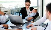 Una mujer sostiene a su bebé durante una reunión de trabajo