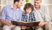 Abuelo, padre e hijo leen juntos un libro