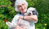 Una mujer mayor sonríe mientras sostiene a un perro en brazos