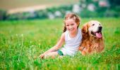 Niña sonríe sentada junto a su perro en el campo