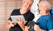 Un hombre mayor muestra a otro su tablet con la aplicación