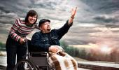 Una mujer sonriente empuja la silla de ruedas de un paciente con ELA