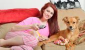 Una chica y su perro viendo la televisión