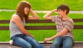 Un niño y una niña se sonríen sentados en un banco