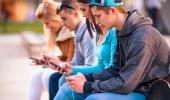 Varios adolescentes consultan las redes sociales en sus móviles