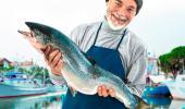 Un pescador sujeta un salmón en sus manos