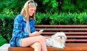 Una joven consulta en su móvil dónde puede ir con su perrito, tumbado junto a ella