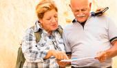 Una pareja de adultos mayores consulta una guía de viajes