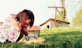 Una niña observa a unos pollitos en una granja