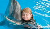 Una niña abraza a un delfín en el agua