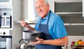 Hombre mayor a punto de probar un guiso en la cocina