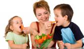 Una madre da verduras a sus hijos pequeños