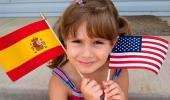 Niña sosteniendo una bandera española y otra estadounidense