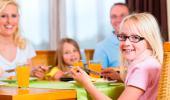 Familia enseñando a sus hijos buenos modales en la mesa