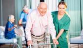 Una cuidadora ayuda a un anciano en una residencia