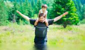 Un hombre cruza un arroyo con su hijo a hombros