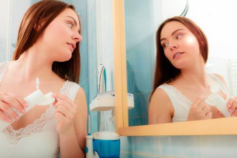 Una joven se limpia el rostro con agua micelar frente al espejo