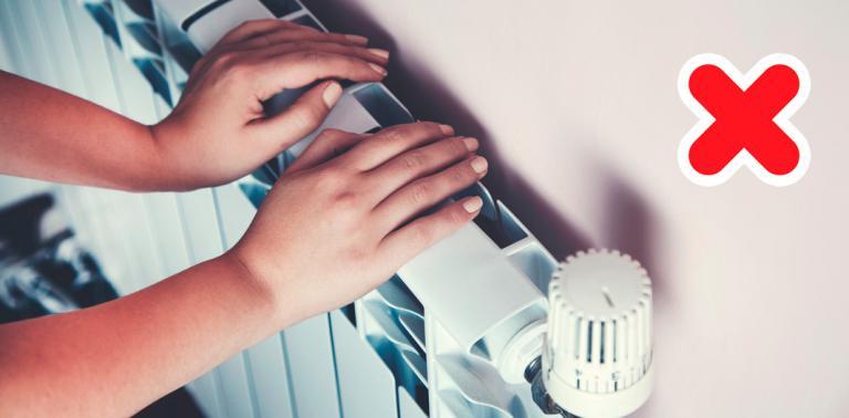 Mujer con sabañones poniendo las manos sobre la calefacción