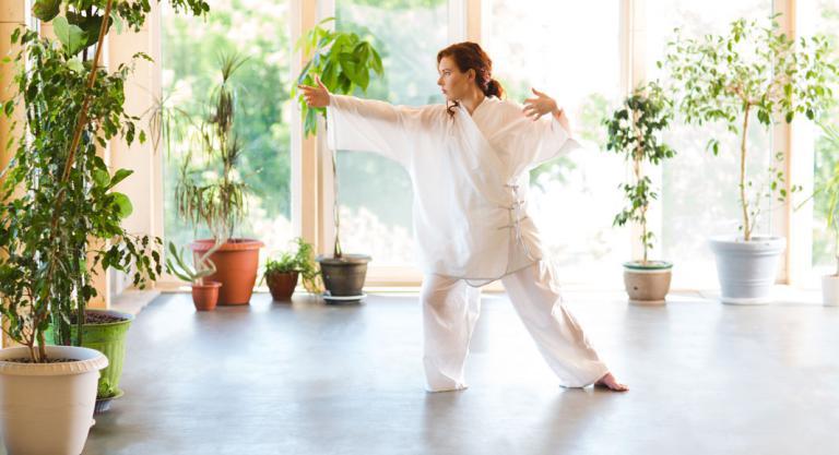 Mujer practicando taichi en casa