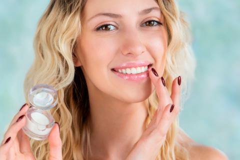 Mujer aplicándose protector labial para mantener sus labios hidratados