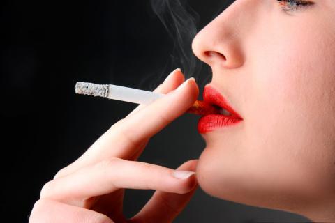 Mujer con los labios pintados fumando un cigarrillo