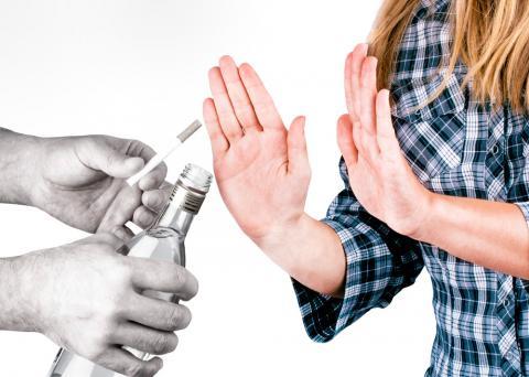 Una mujer hace un gesto de rechazo a la bebida alcohólica y el cigarrillo que le ofrecen
