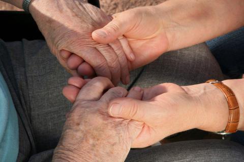 Agarrando las manos de paciente con síntomas del alzhéimer