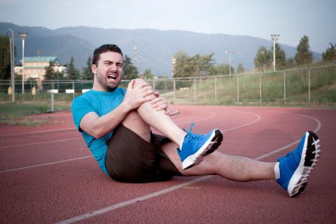 Deportista con síntomas de un esguince de rodilla