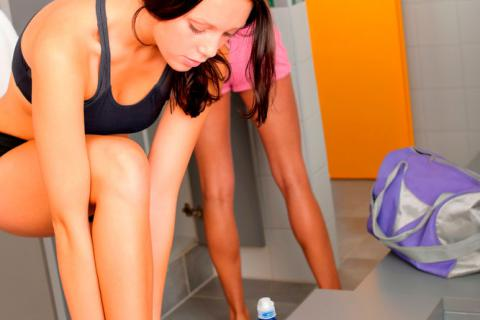 Mujer vistiéndose con ropa deportiva antes de hacer ejercicio