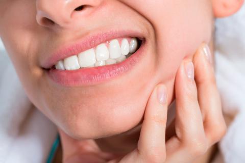 Una mujer se toca la mandíbula dolorida