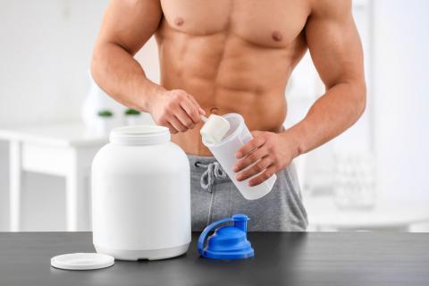 Hombre con músculos tomando suplementos para el deporte llamados gainers