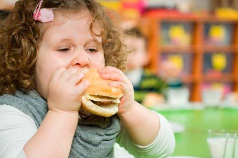 Niña con obesidad infantil comiendo una hamburguesa