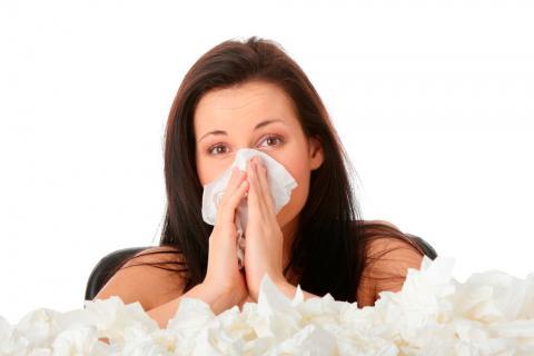 Una mujer con rinitis se suena la nariz junto a una pila de pañuelos de papel usados