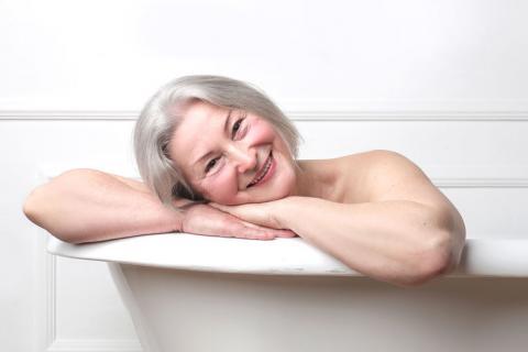 Mujer mayor dándose un baño caliente para reducir el riesgo cardíaco