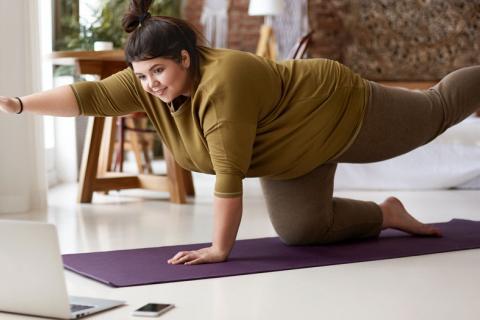 Mujer con obesidad realizando pilates en casa
